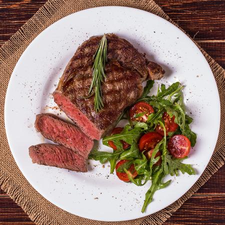 Foto per Ribeye steak with arugula and tomatoes on  dark wooden background. - Immagine Royalty Free