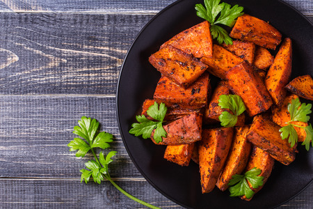 Photo pour Homemade Cooked Sweet Potato with spices and herbs on dark background. - image libre de droit