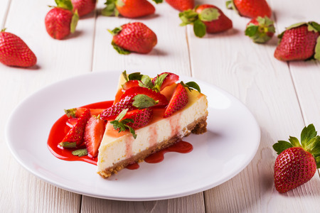 Photo for Delicious homemade cheesecake with strawberries  on  white wooden table. - Royalty Free Image