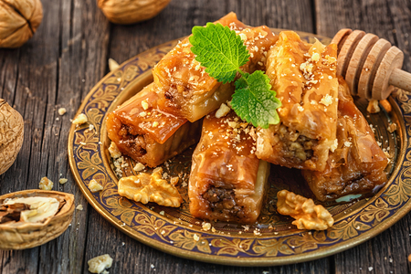 Photo for Traditional arabic dessert Baklava with honey and walnuts, selective focus. - Royalty Free Image