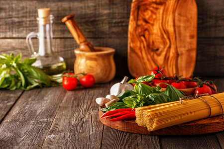 Photo pour Products for cooking - pasta, tomatoes, garlic, pepper, and basil on the old wooden background. - image libre de droit