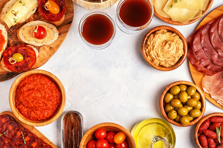 Foto de Typical spanish tapas concept. Concept include slices jamon, chorizo, sausage, bowls with olives, tomatoes, anchovies,  mashed chickpeas, cheese. - Imagen libre de derechos