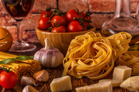Foto de Products for cooking - pasta, tomatoes, garlic, olive oil and red wine. Selective focus. - Imagen libre de derechos