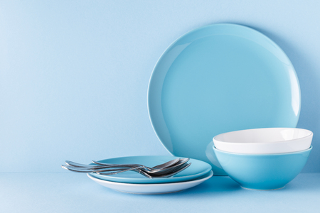 Photo pour Crockery and cutlery on a blue pastel background with copy space. - image libre de droit