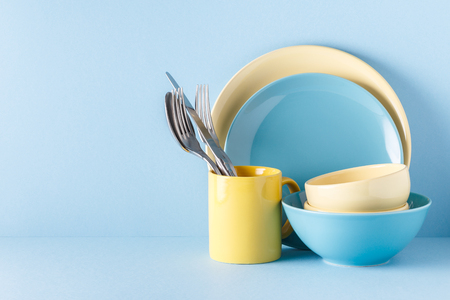 Photo for Crockery and cutlery on a blue pastel background with copy space. - Royalty Free Image