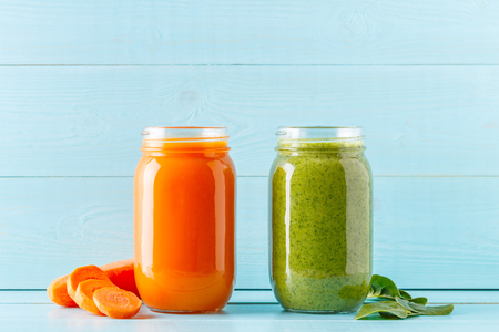 Photo for Orange/green colored smoothies / juice in a jar on a blue background. - Royalty Free Image