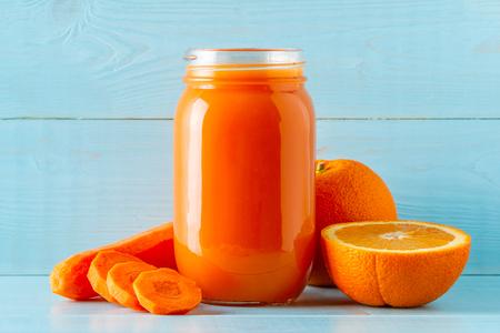 Foto de Orange-colored smoothies / juice in a jar on a blue background. - Imagen libre de derechos