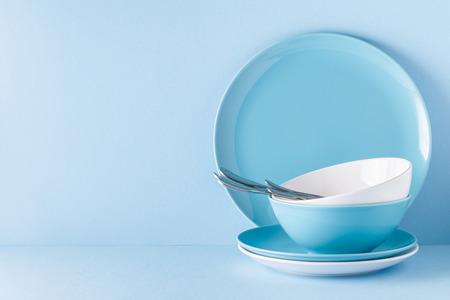 Photo pour Crockery and cutlery on a blue pastel background with copy space. - image libre de droit
