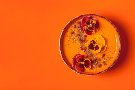 Photo for Smoothie bowl with edible pansy flowers, chia seeds, goji berries, top view. - Royalty Free Image