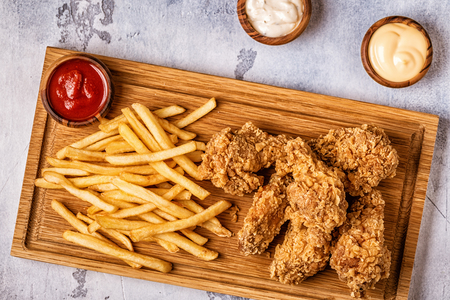 Photo pour Fried chicken wings with french fries, top view. - image libre de droit