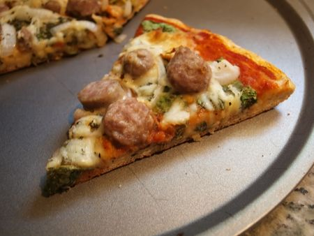 a slice of fresh baked sausage, spinach and onion pizza
