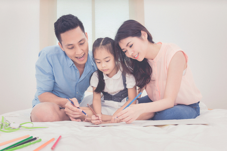 Photo for Happy family in the bedroom,Asian father and mother teaching her daughter child to studying at home.Photo series of family, kids and happy people concept. - Royalty Free Image