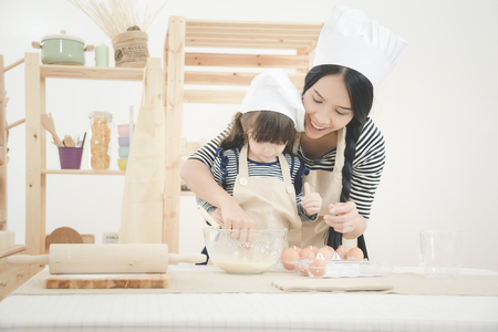 Foto per Happy family in the kitchen. Asian mother and her daughter preparing the dough to make a cake.Photo design for family, kids and happy people concept. - Immagine Royalty Free