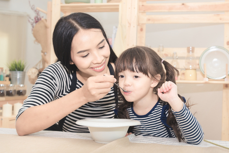 Photo pour Happy family of asian mom feeding healthy breakfast to her cute daughter in the morning. Photo series of family, kids and happy people concept. - image libre de droit
