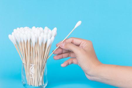 Foto de Cotton bud wood stick or cotton swab on background with hand - Imagen libre de derechos