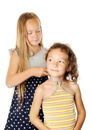 Girl fixing her sister hair, on a white background