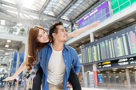 Foto de Young asian couple having fun and playing at airport terminal. Happy asia lovers are traveling honeymoon trip by airplane. Asia tourism, or holiday vacation travel concept. - Imagen libre de derechos