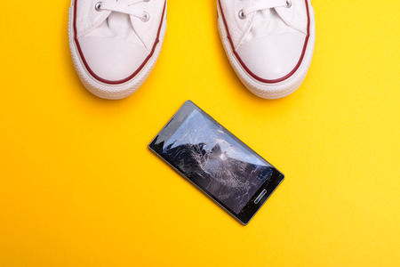 Photo for Mobile phone with broken screen on floor - Royalty Free Image