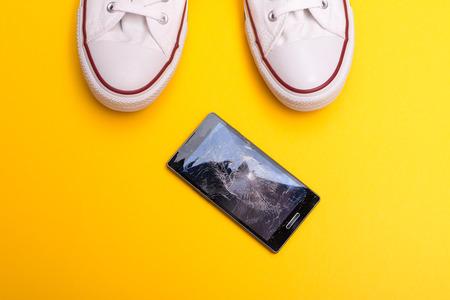 Foto de Mobile phone with broken screen on floor - Imagen libre de derechos