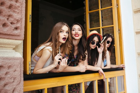 Foto de four beautiful young girls look out from the window - Imagen libre de derechos