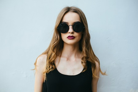 Photo pour Attractive fashion woman in black dress with sunglasses posing near white wall - image libre de droit