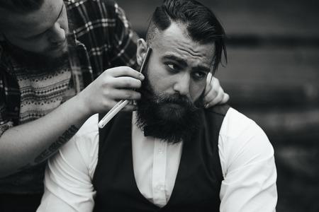 Photo pour barber shaves a bearded man in vintage atmosphere - image libre de droit