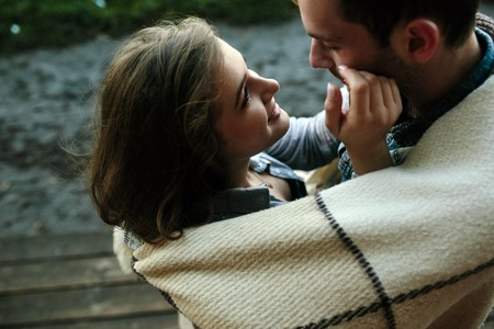 Foto de Young couple in love wrapped in plaid standing and looking at each other - Imagen libre de derechos