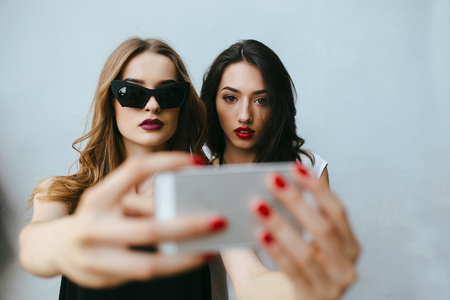 Two teenage girlfriends taking a selfie with smartphone