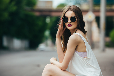 Foto de beautiful girl in sunglasses sitting on the asphalt - Imagen libre de derechos