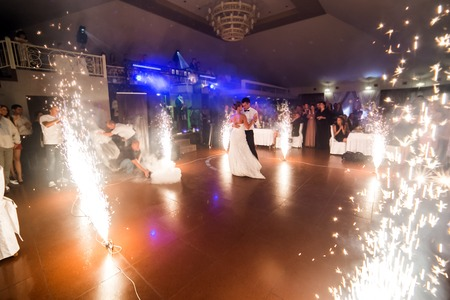 Photo pour beautiful bride and groom dancing the first dance between fireworks - image libre de droit