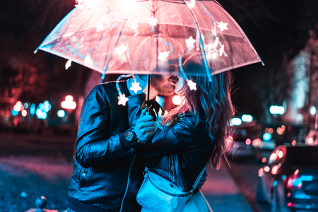 Photo for Guy and girl kissing under an umbrella - Royalty Free Image