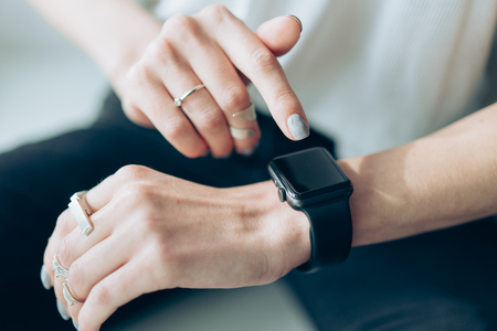 Foto per Womans hand touching the screen of a smart watch - Immagine Royalty Free