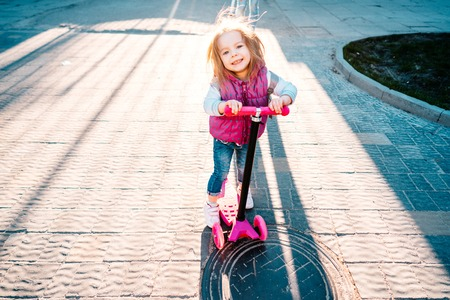 Photo for Little girl with blonde hair rides on scooter - Royalty Free Image