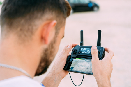 Photo for Guy controls drone with remote control - Royalty Free Image