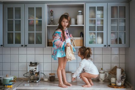 Photo pour two little girls are looking for cookies - image libre de droit