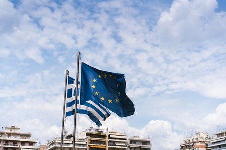 Photo pour Flags of Greece and the European Union are developing on flagpoles. - image libre de droit