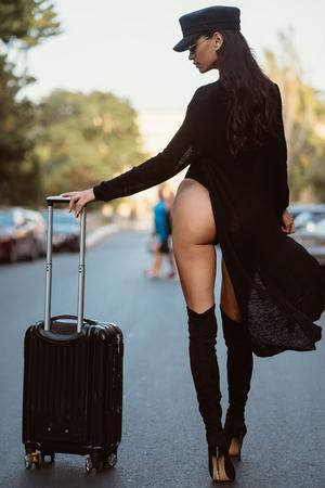 Foto de A young sexy woman in a black leotard posing on a camera - Imagen libre de derechos