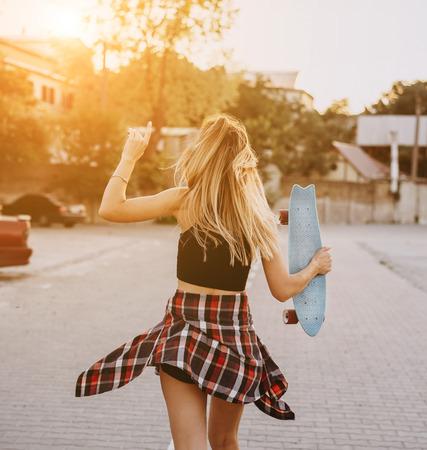 Photo pour Young girl with a skateboard on a car park. - image libre de droit