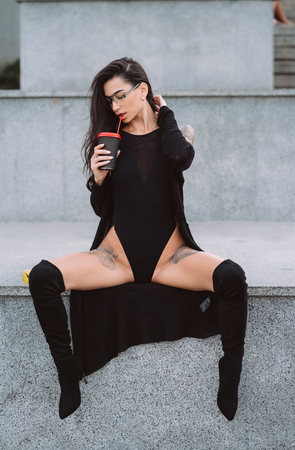 Photo pour Woman in a sexy position is drinking street coffee. - image libre de droit