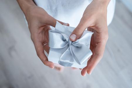 Photo pour Woman hands holding Gift box with white bow, close-up - image libre de droit