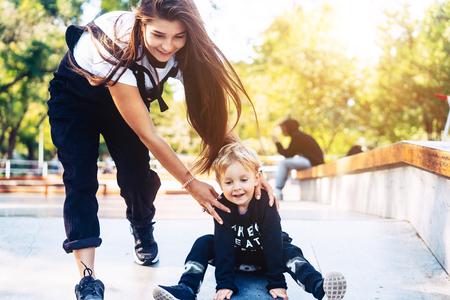 Photo pour Young mother teaches her little boy to ride a skateboard - image libre de droit