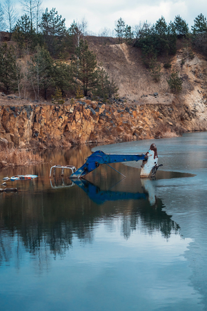 Photo for Flooded excavator in a large lake near the basaltic quarry - Royalty Free Image