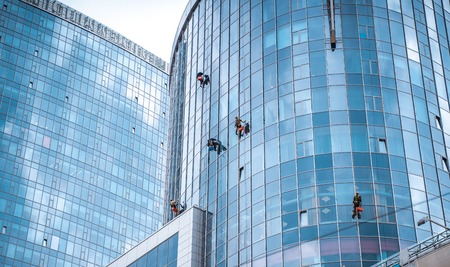 Foto de Several workers washing windows in the office building - Imagen libre de derechos
