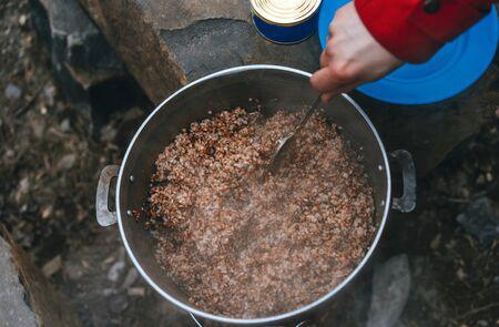 Photo pour Camper preparing meal in large kettle on campfire - image libre de droit