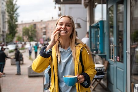 Photo for Enchanting blonde young woman with smartphone while on the street - Royalty Free Image