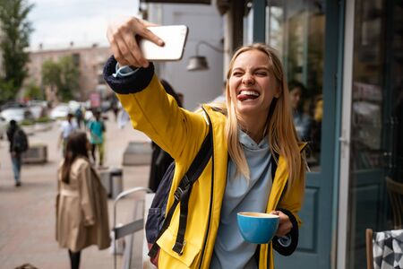 Photo for Enchanting blonde young woman with smartphone take selfie on the street - Royalty Free Image