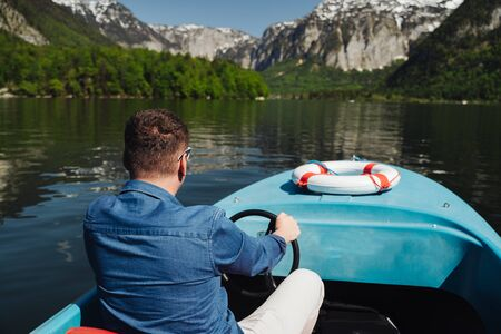 Photo for Handsome young guy controls a motorboat on a mountain lake - Royalty Free Image
