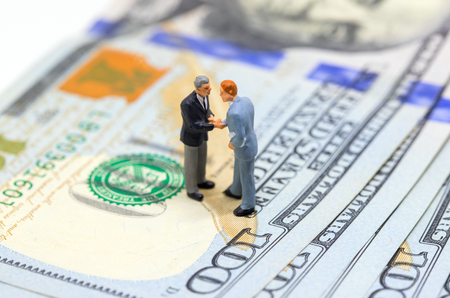 Photo for Businessmen shaking hands on american dollar. Businessmen figurines on money background. Finance growth. Business profit or income concept. Buy and sell transactions for cash money. Corruption payment - Royalty Free Image