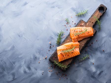 Foto de Raw salmon pieces on wooden board with herbs, salt and spices - Imagen libre de derechos