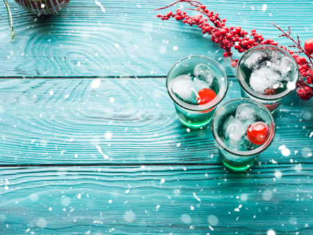 Photo pour Christmas party green alcohol drinks with cherry. Festive aperitif shots and ornaments on wooden dark table. Holiday background with falling snow - image libre de droit